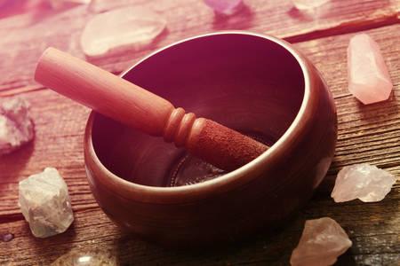 Tibetaanse zangkom met stok met kristallen op houten bord