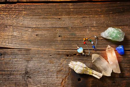 Natuurlijke edelstenen, wit salie en dowsing gereedschap op houten bord