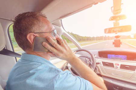 Man using phone while driving the car. Risky driving behaviors concept photo