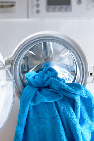 Modern washing machine loaded with blue towel Stock Photo - 84181674