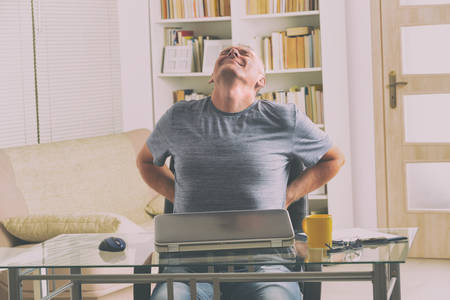 Man in home office suffering from low back pain sitting at a desk with notebook, papers and other objects Stock Photo
