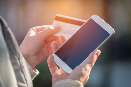 Hands holding credit card and using smart phone outdoor, mobile online payment concept
