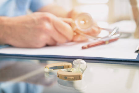 Doctor audiologist and hearing aid on a table