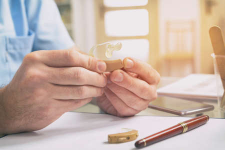 Doctor audiologist holding hearing aid in his hand Banque d'images