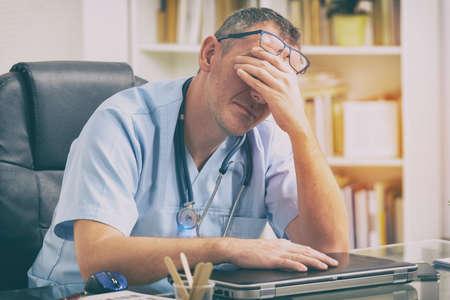 Überarbeiteter Doktor, der in seinem Büro sitzt