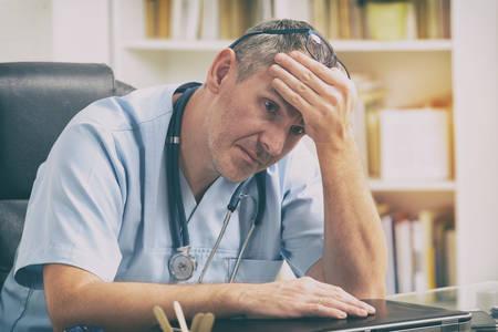 Medico straordinario seduto nel suo ufficio Archivio Fotografico