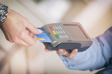 Paying with credit or debit card in wireless payment terminal at shop Stock Photo