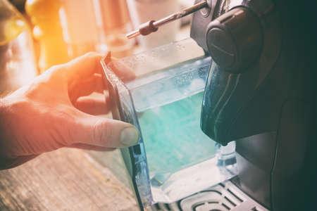 Recharge d'eau dans une machine à café, un récipient dans la main Banque d'images - 91579143