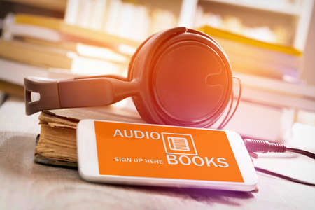Smart phone with audio books application on screen, headphones and the paper books. Concept of listening to audiobooks.