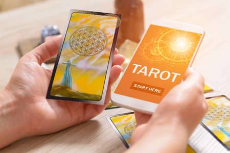 Tarot cards and smartphone with modern fortunetelling application on screen as a concept of psychic advisor or newest ways of divination Foto de archivo