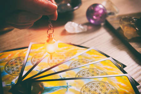 Tarot cards dowsing tool in hand and crystals as a concept of psychic advisor or ways of divination Stock Photo - 101353591