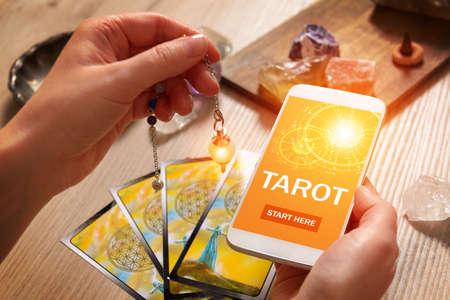 タロットカードは、精神的なアドバイザーや占いの最新の方法の概念として、画面上の近代的な占いアプリケーションと手とスマートフォンでツー 写真素材