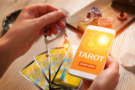 Tarot cards dowsing tool in hand and smartphone with modern fortunetelling application on screen as a concept of psychic advisor or newest ways of divination