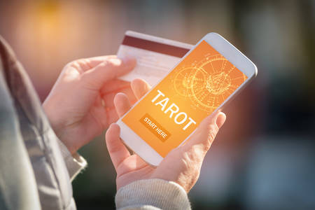 Smartphone with modern fortunetelling application on screen and hand with a credit card ready to pay for access to the application. Pay for divination concept Stock Photo