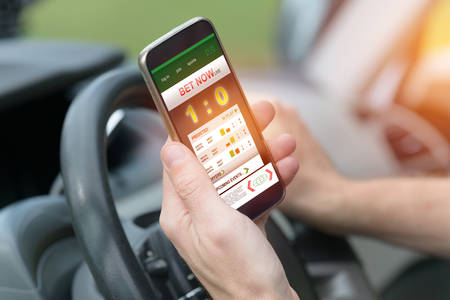 Betting on sports, holding smart phone with working online betting mobile application while driving a car