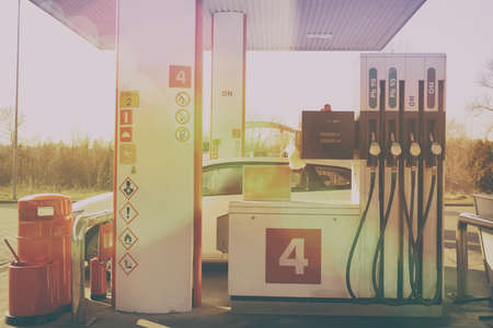European gas station with white car and fuel pumps.