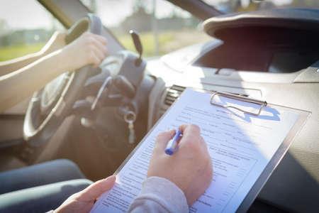 Prüfer, der Führerscheinstraßentestformular ausfüllt, das mit ihrem Studenten innerhalb eines Autos sitzt Standard-Bild