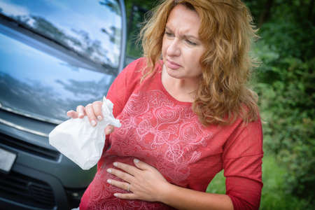 Woman suffering from motion sickness in a car and holding sick bag Stockfoto - 103738566
