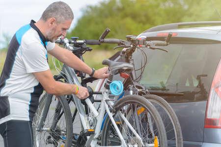 Man wearing sportswear loading bicycles on the bike rack mounted to a car towbar