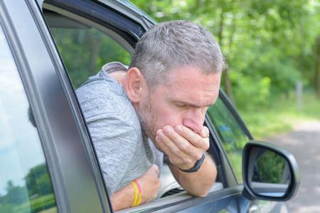 Man suffering from motion sickness in a car