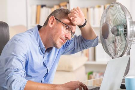 Mężczyzna cierpi na upał podczas pracy w biurze i próbuje się ochłodzić przy wentylatorze
