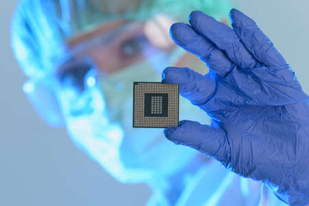 An engineer working in a laboratory wearing a special uniform and protective gloves holds new processor in hands and examines it