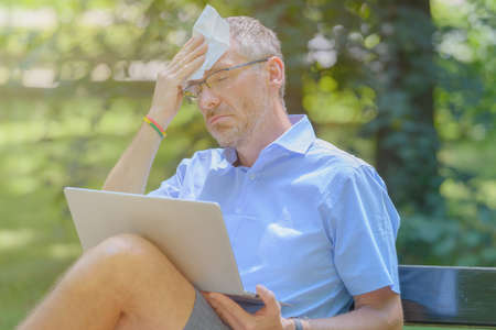 Man suffers from heat while working with laptop in the park and wiping his forehead with tissue