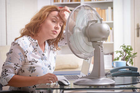 Woman suffers from heat while working in the office and tries to cool off by the fan Stock Photo