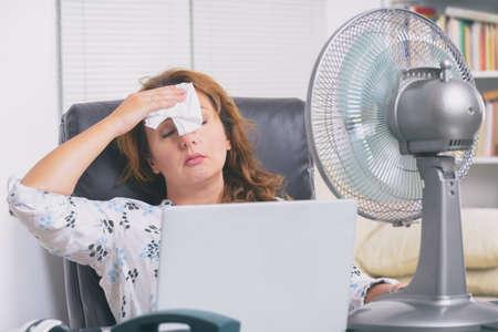 Mujer sufre de calor mientras trabaja en la oficina e intenta refrescarse junto al ventilador Foto de archivo