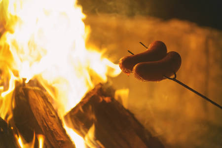 Roasting sausages on the fire. Summer picnic or camping concept Stock Photo