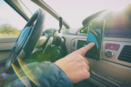 Woman using smart phone as navigation while driving the car. Risky driving behaviors concept Imagens