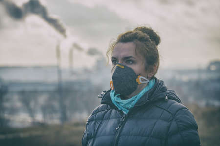 Woman wearing a real anti-pollution, anti-smog and viruses face mask; dense smog in air. 스톡 콘텐츠
