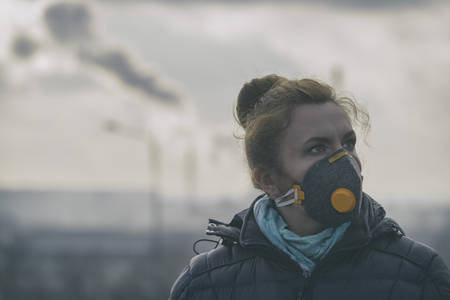 Woman wearing a real anti-pollution, anti-smog and viruses face mask; dense smog in air. Stock Photo