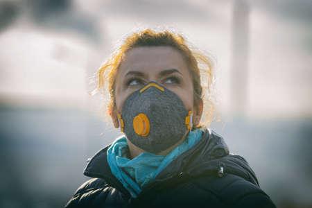 Mujer vistiendo una verdadera mascarilla anti-contaminación, anti-smog y virus; smog denso en el aire.