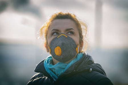 Woman wearing a real anti-pollution, anti-smog and viruses face mask; dense smog in air. Banco de Imagens