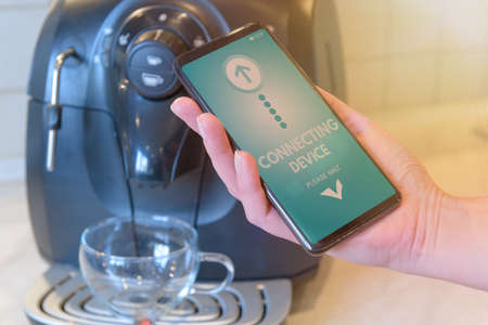 Connecting coffee machine with smart phone. Smart home and Internet of Things IoT concept