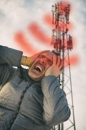 Man holding his head near the BTS. Harmful radiation from cellular network transmitters concept Imagens