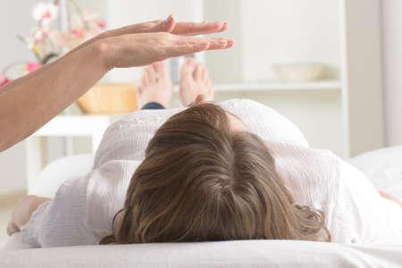 Professional Reiki healer doing reiki treatment to young woman Stockfoto