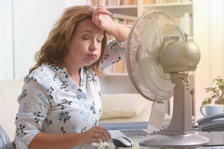 Frau leidet unter Hitze während der Arbeit im Büro und versucht, sich durch den Ventilator abzukühlen