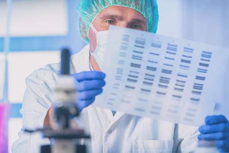 Científico analizando la secuencia de ADN en el laboratorio moderno Foto de archivo
