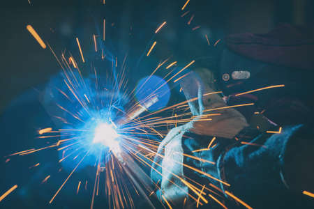 Industrial Worker at the factory or workshop welding steel elements