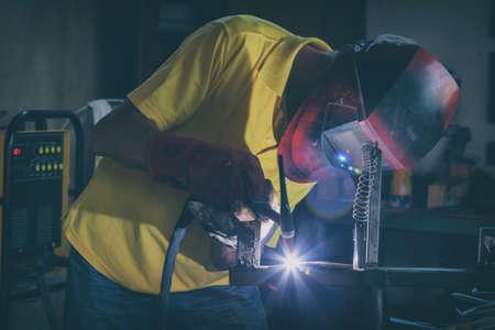 Industrial Worker at the factory or workshop welding steel elements