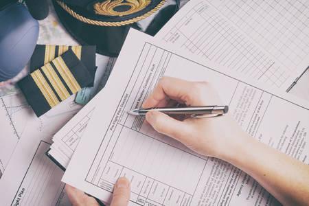 Nahaufnahme einer Flugzeugpilotenhand, die eine Checkliste vor dem Flug ausfüllt und die Wettervorhersage mit Ausrüstung wie Hut, Schulterklappen und anderen Dokumenten im Hintergrund hält