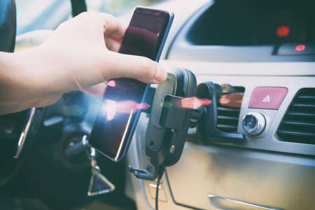 Modern wireless smartphone charging in a car with a hand putting a phone on it. Dashboard in background. Reklamní fotografie
