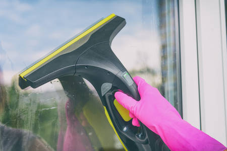 Cleaning windows with portable professional vacuum cleaner. Hand in protective glove