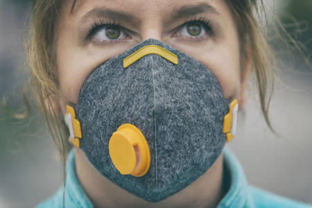 Woman wearing a real anti-pollution, anti-smog and viruses face mask; dense smog in air. Фото со стока - 132281602