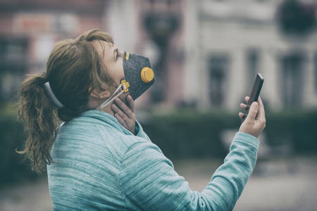 Woman wearing a real anti-pollution, anti-smog and viruses face mask and checking current air pollution with smart phone app Фото со стока - 132281606