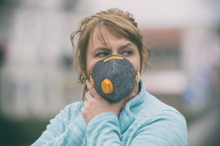 Woman wearing a real anti-pollution, anti-smog and viruses face mask; dense smog in air. Фото со стока - 132281610
