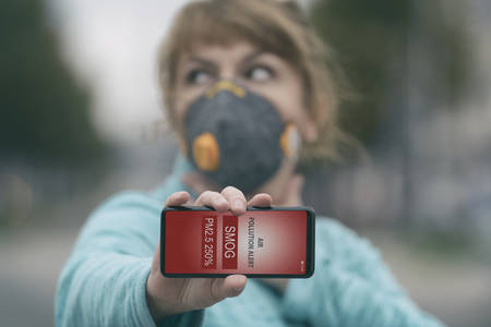 Woman wearing a real anti-pollution, anti-smog and viruses face mask and checking current air pollution with smart phone app