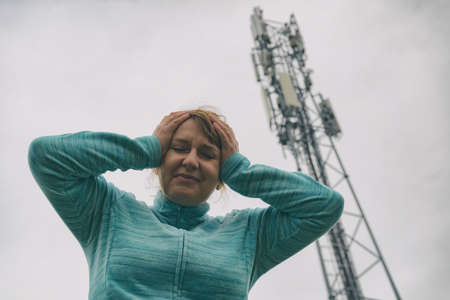 The woman is holding her head near the BTS. Harmful radiation from cellular 5G network transmitters concept Фото со стока